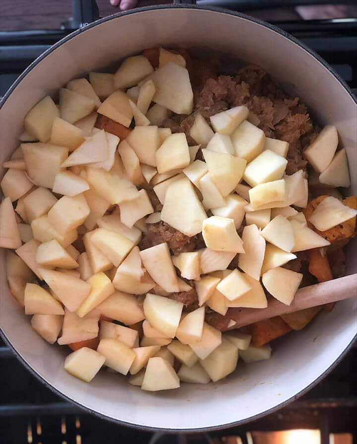 A pot with apples, onions, and squash for butternut squash soup.