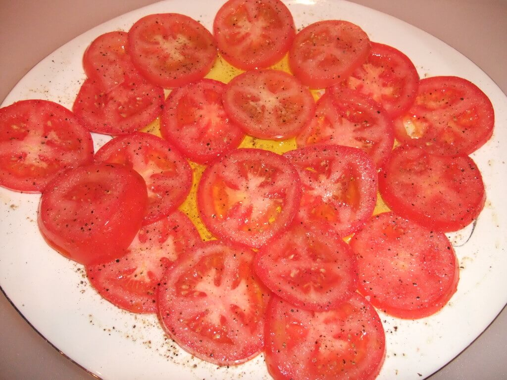 Sliced tomatoes on a plate with olive oil.