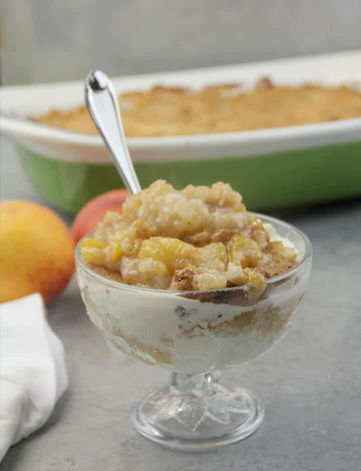 A serving of peach cobbler with ice cream.