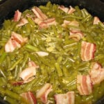 A photo of cooked southern green beans with bacon.