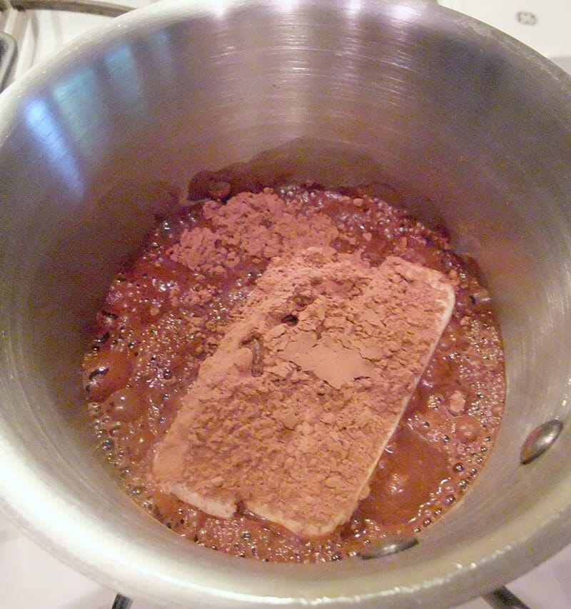 Chocolate sheet cake mixing butter and cocoa in saucepan