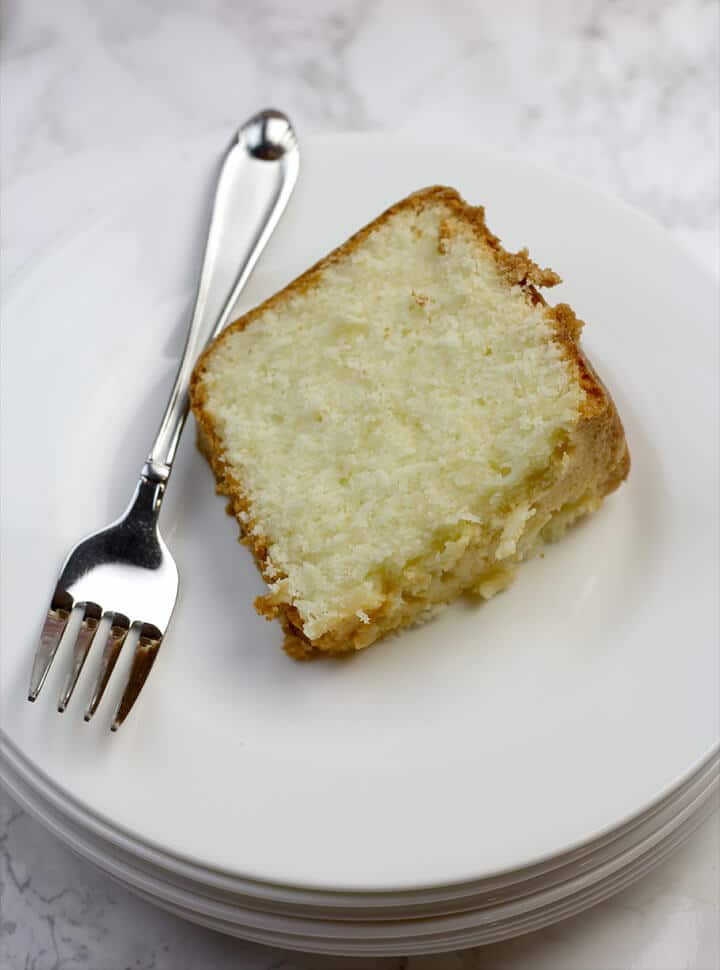 Slice of cream cheese pound cake on a plate.
