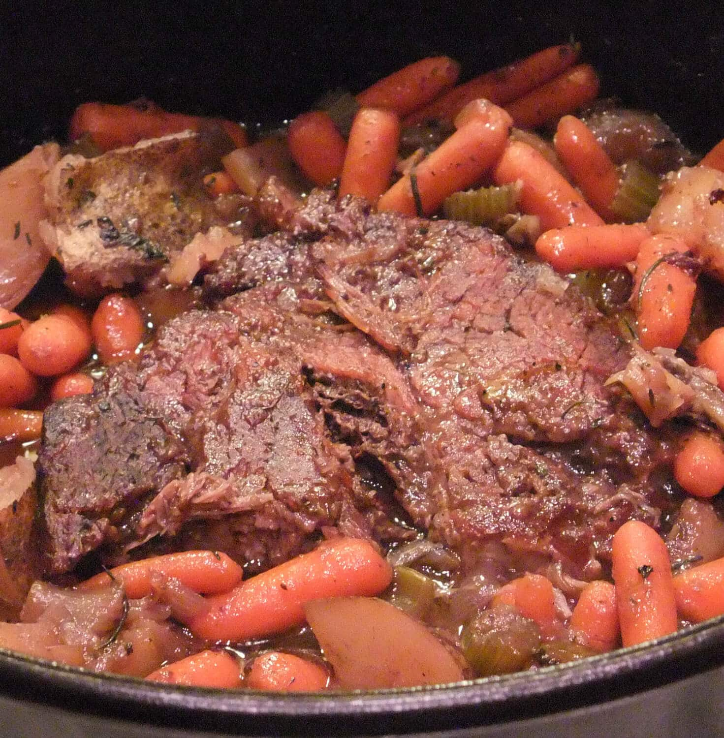 Cooked Pot Roast with vegetables in a classic sauce in a large Dutch oven.