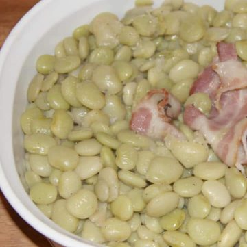 Cooked butter beans recipe in a dish with bacon.