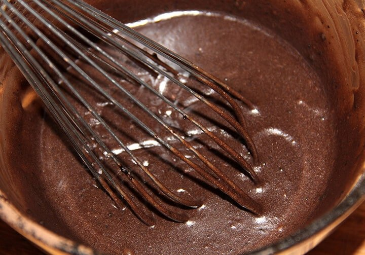 Bowl with whisk mixing cocoa into butter and sugar for fudge pie.