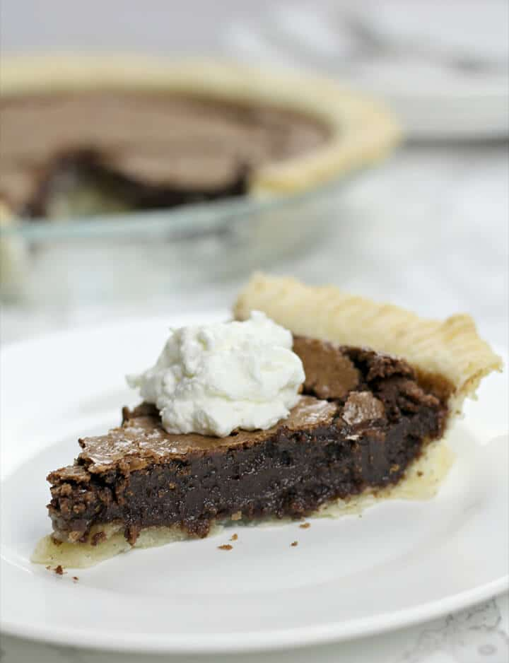 A slice of fudge pie topped with a dollop of whipped cream.