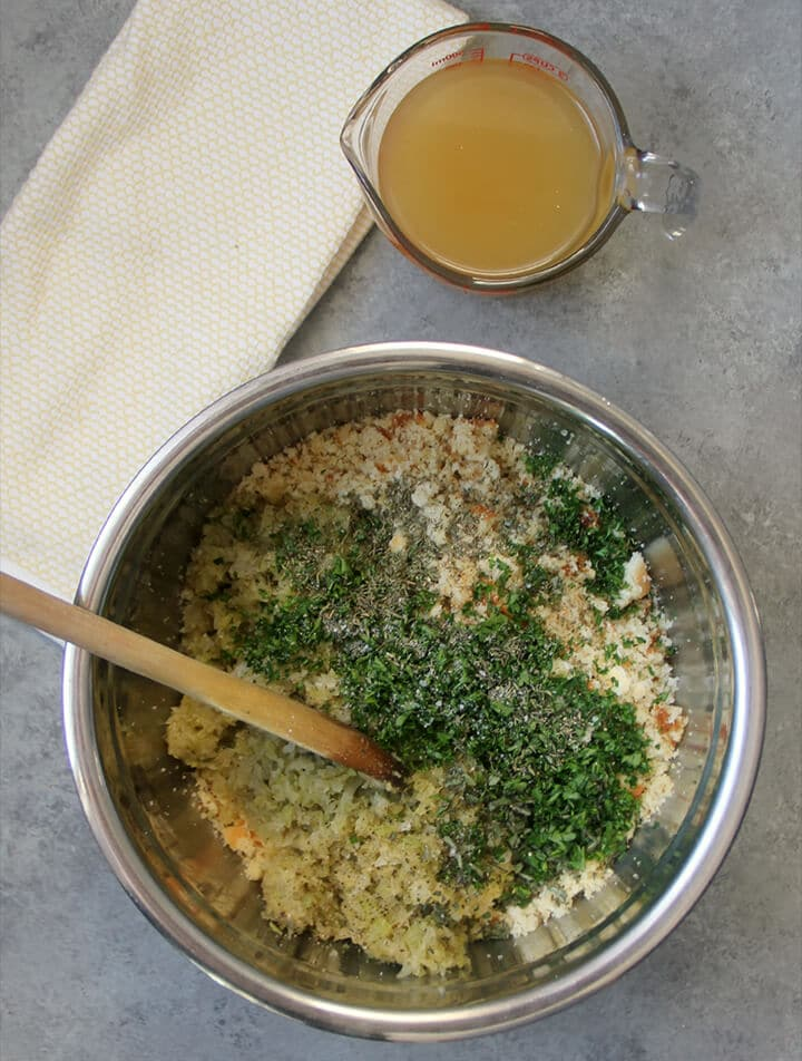 Parsley, sage, cornbread, biscuits in a bowl with a cup of stock sitting nearby.
