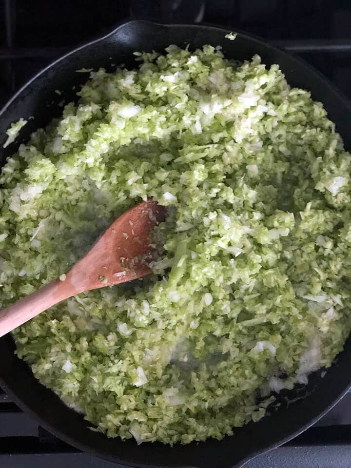 Celery and onions in a skillet with a wooden spoon for cornbread dressing.