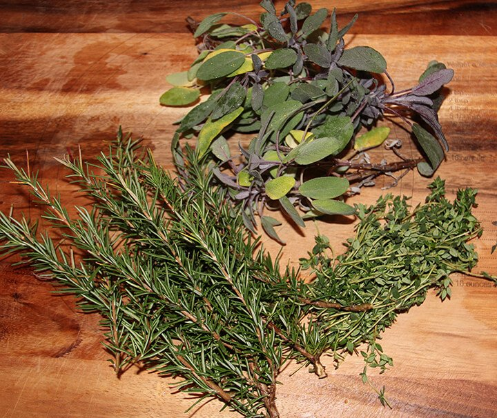 Fresh herbs on a cutting board to use for herb butter.