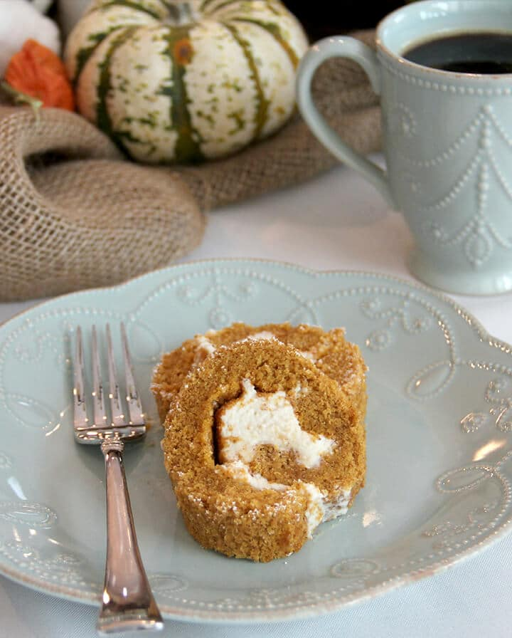 A slice of pumpkin roll on a plate with a fork.