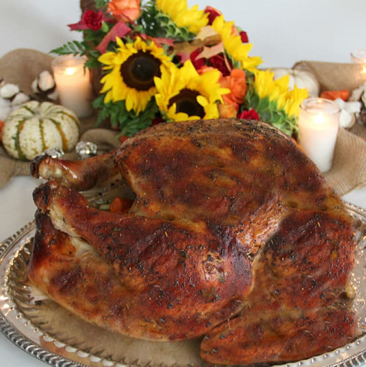 Roasted turkey on a platter with flowers in the background for Thanksgiving dinner menu.