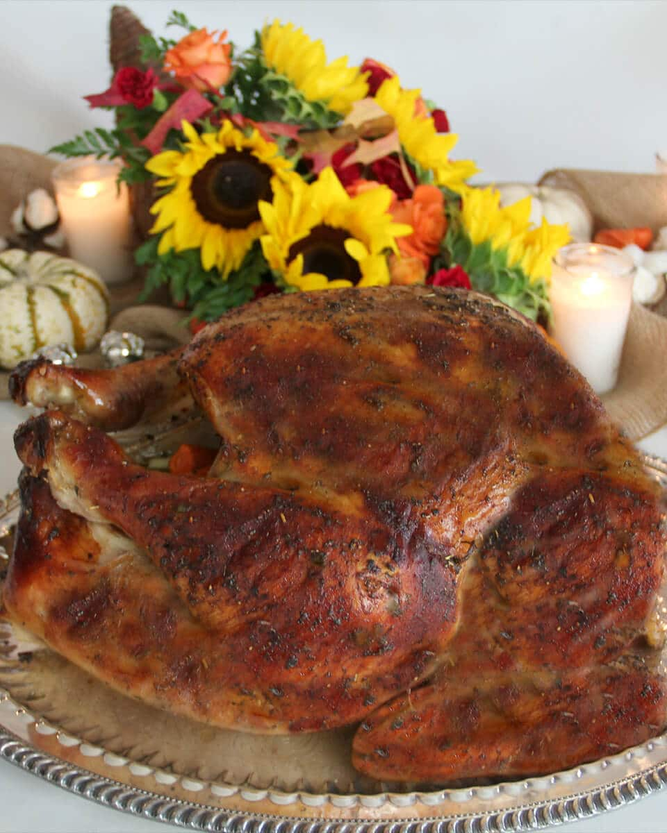 Side view of whole roasted turkey with flowers in the background.