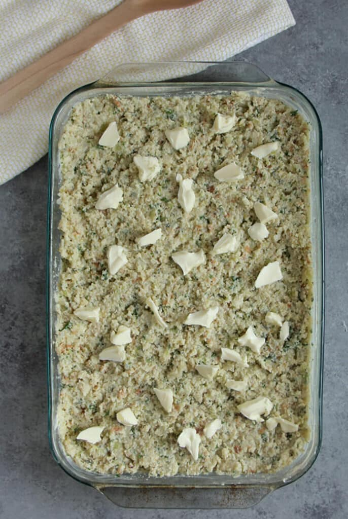 Unbaked cornbread dressing dotted with butter in a baking dish.