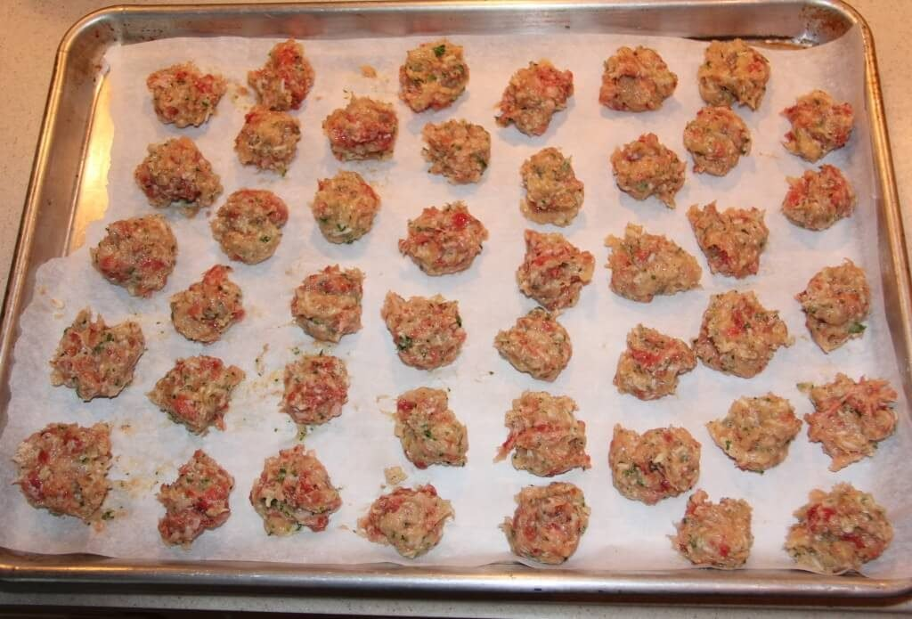 Chicken meatballs on parchment paper on a baking sheet ready to bake for Italian Wedding Soup.