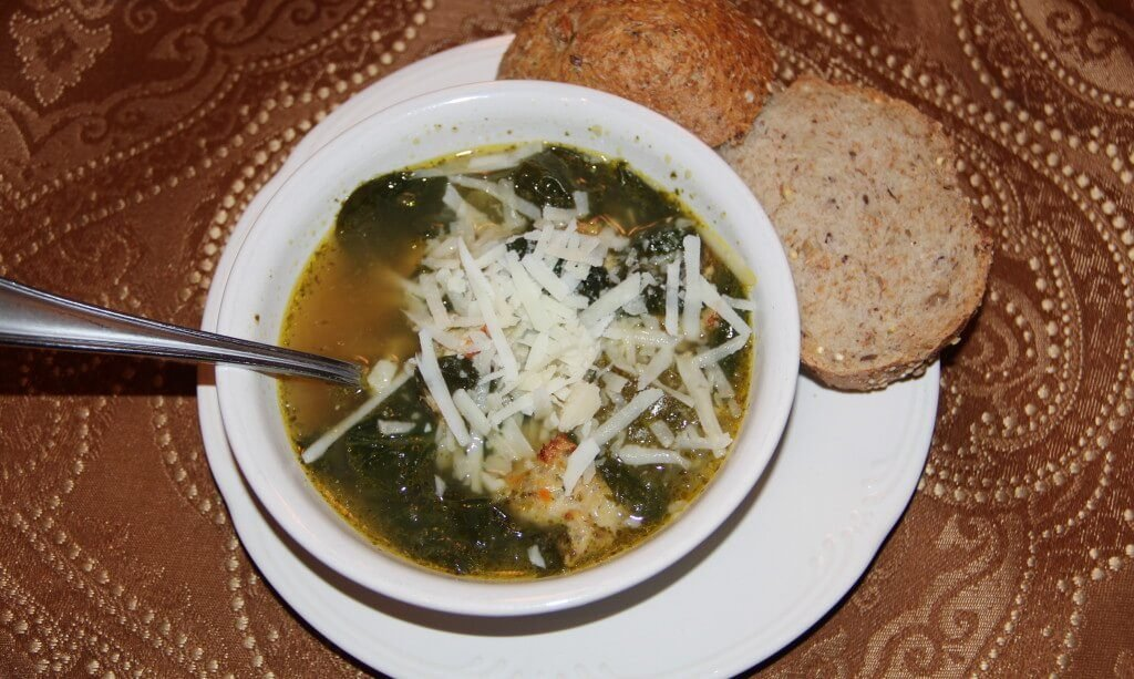 A bowl of Italian Wedding soup with cheese on top and bread on plate.