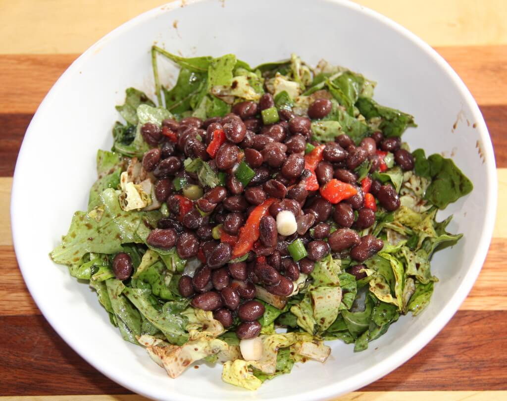 black bean salad on a bowl of greens in a white bowl
