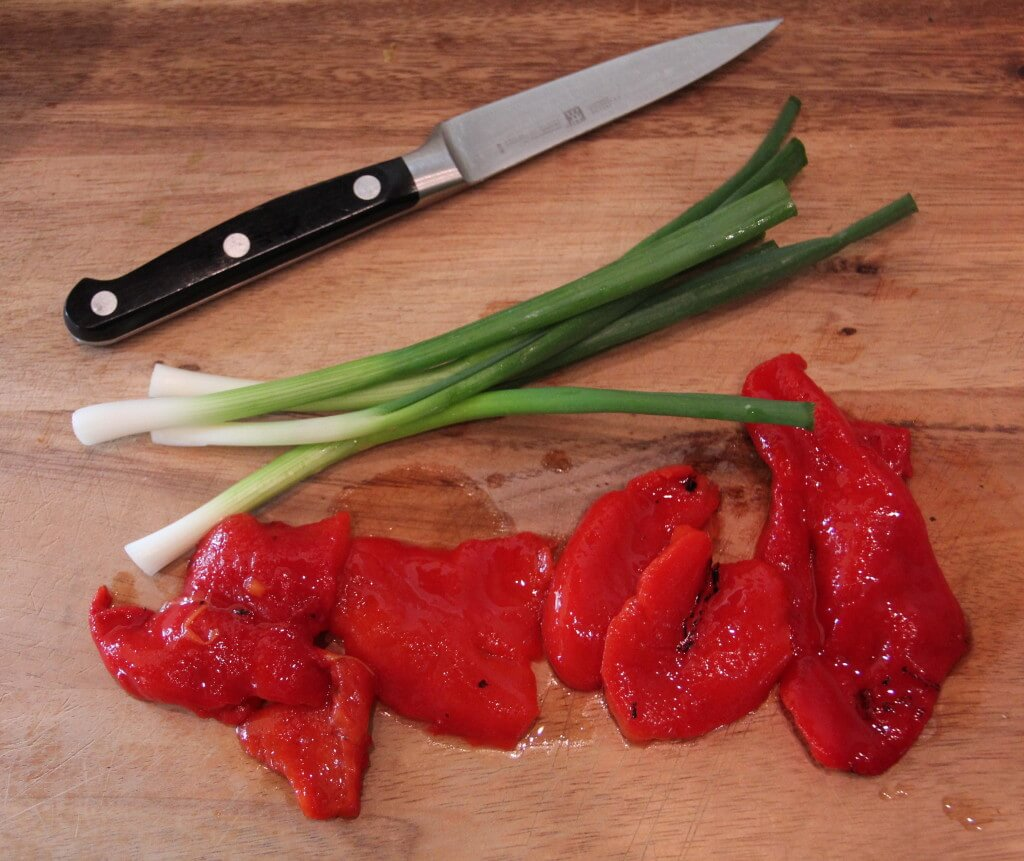 roasted red pepper and green onions on a cutting board with a knife