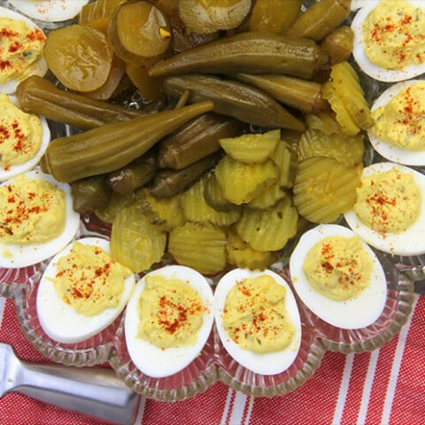 Closeup of Southern deviled eggs on a platter with pickles in the center.