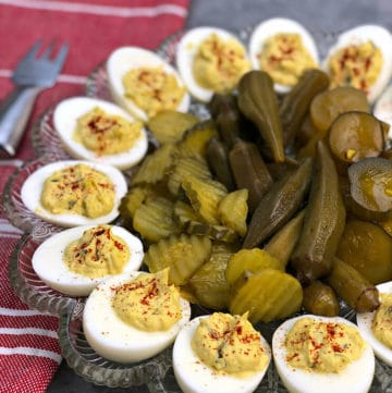 A platter of Southern deviled eggs with pickles on a red towel.