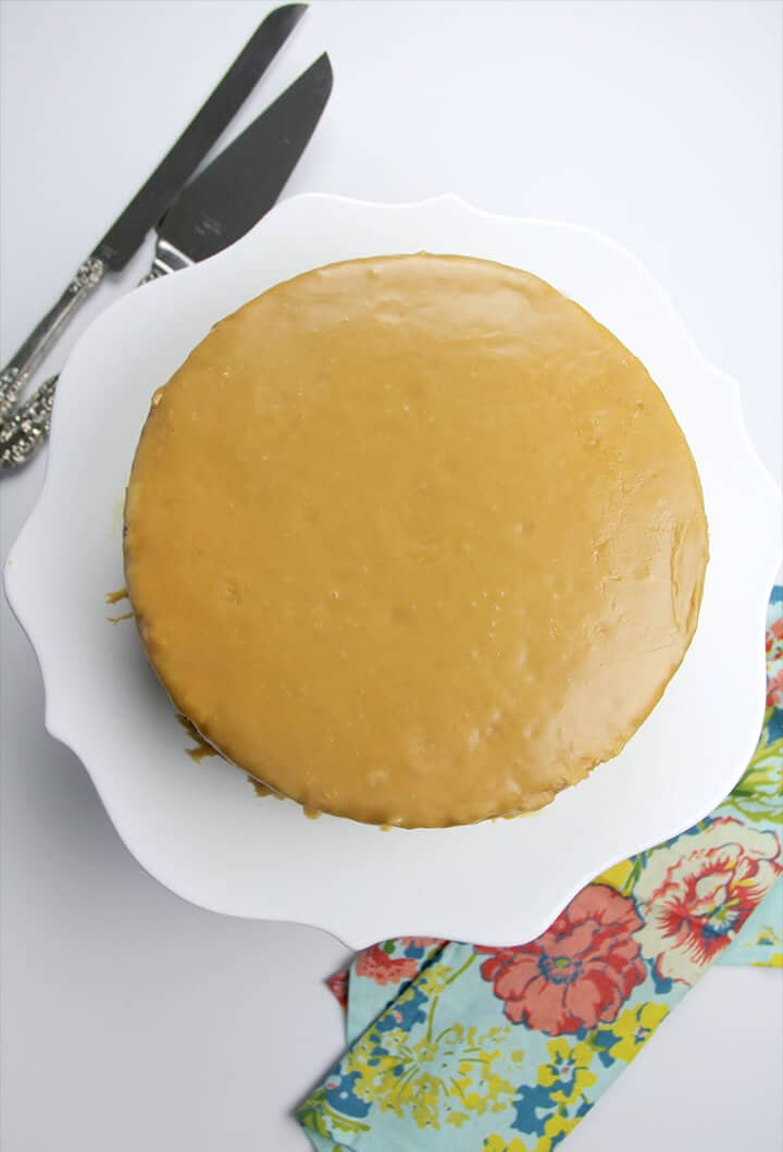Overhead view of whole caramel cake on white stand with knife and server.