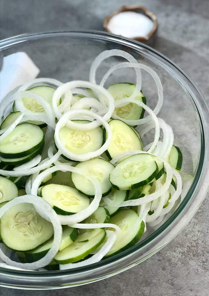 Cucumbers and onions sliced in a bowl for cucumber salad.