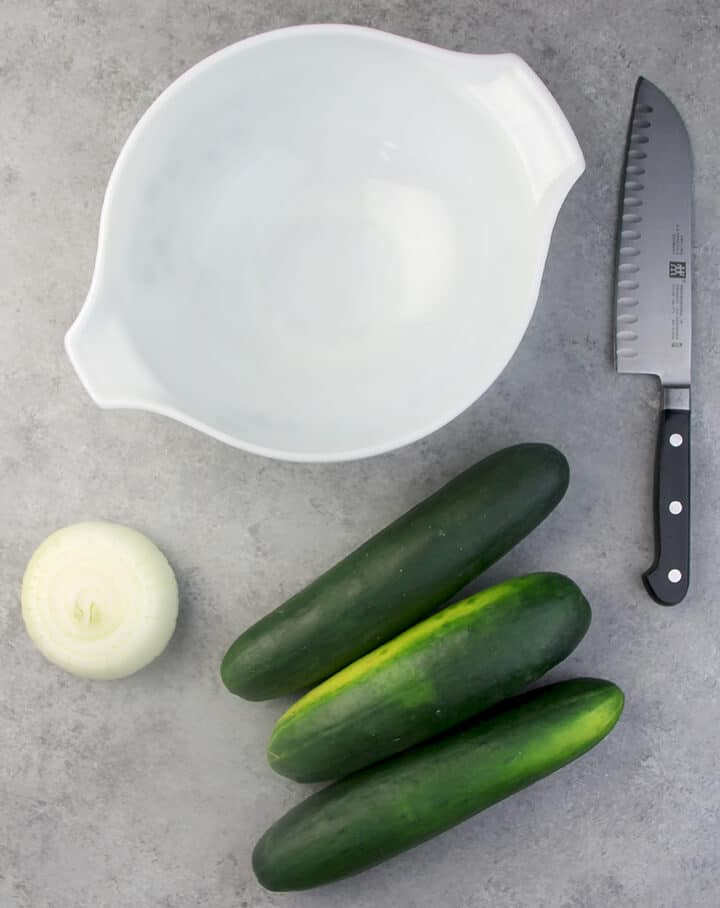 Cucumbers and onions on a table with a bowl and knife.