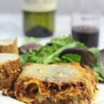 Serving of lasagna without ricotta on a plate with salad.
