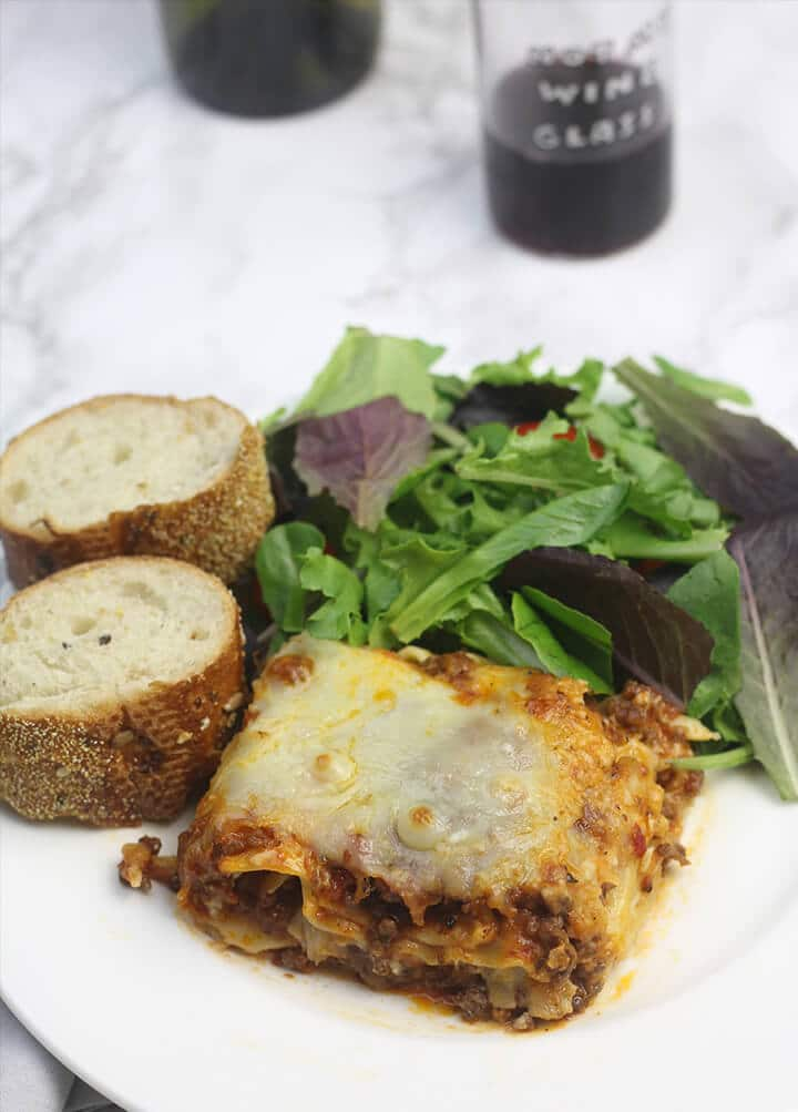 Serving of lasagna on a plate with salad and bread.