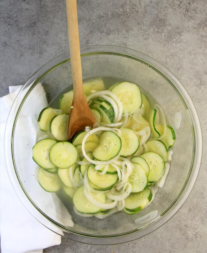 Old-fashioned cucumbers and onions in vinegar in a bowl.