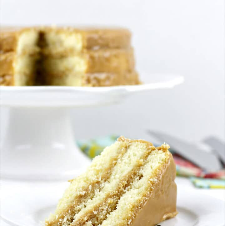 Slice of caramel cake on a plate with whole cake in background.