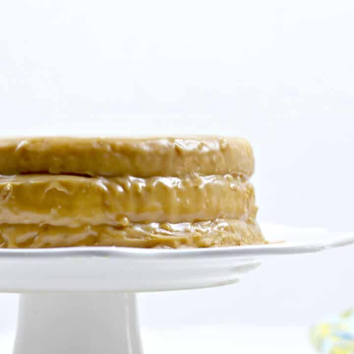 Side of a whole caramel cake on a white cake stand.