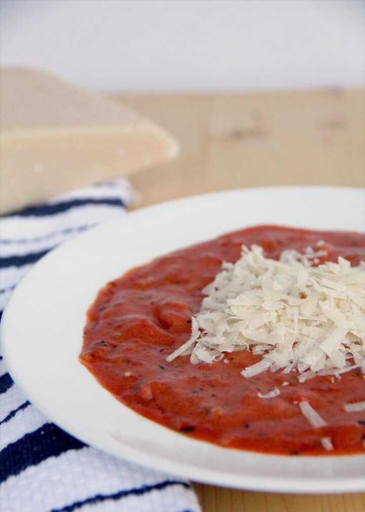 Tomato soup in a bowl with grated cheese on top.