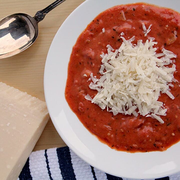 This Easy Tomato Soup Recipe is ready in under an hour! It's made with canned tomatoes, dried herbs, fresh onion, and cream—just add a grilled cheese!