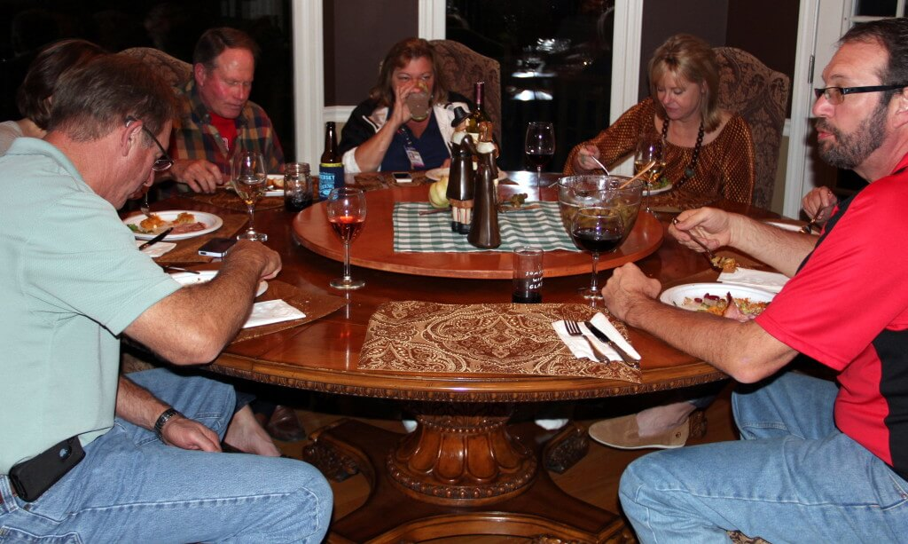 friends gathered around a round table eating thanksgiving dinner.