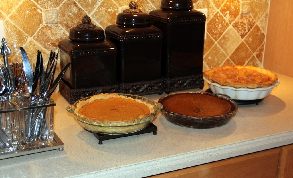 Pumpkin Pie with Gingersnap Crust, Sweet potato pie, and apple pie on a counter.