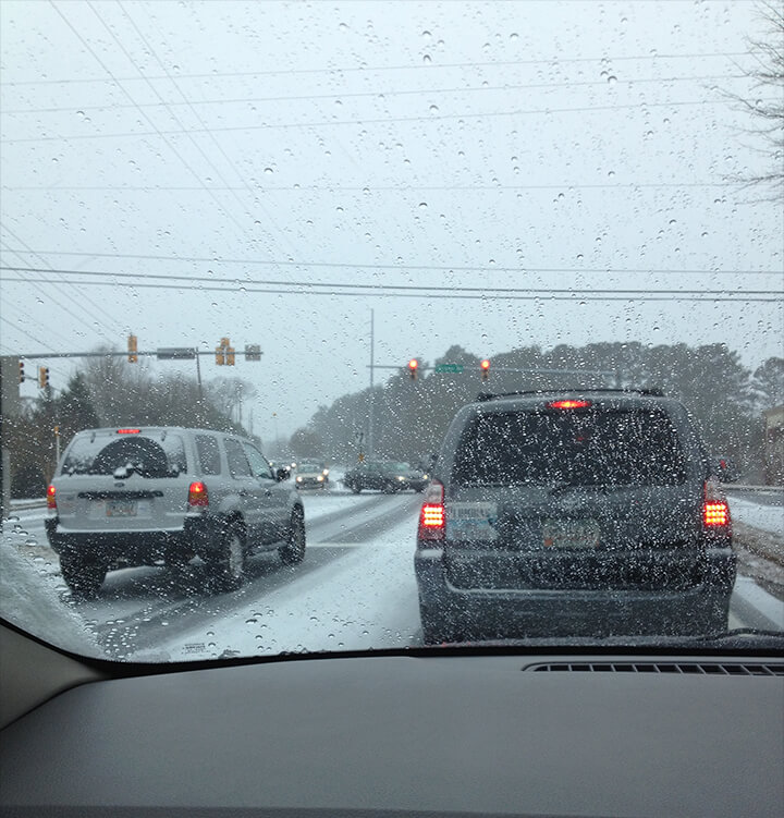 Cars and trucks driving on icy road after Atlanta snowpocalypse.