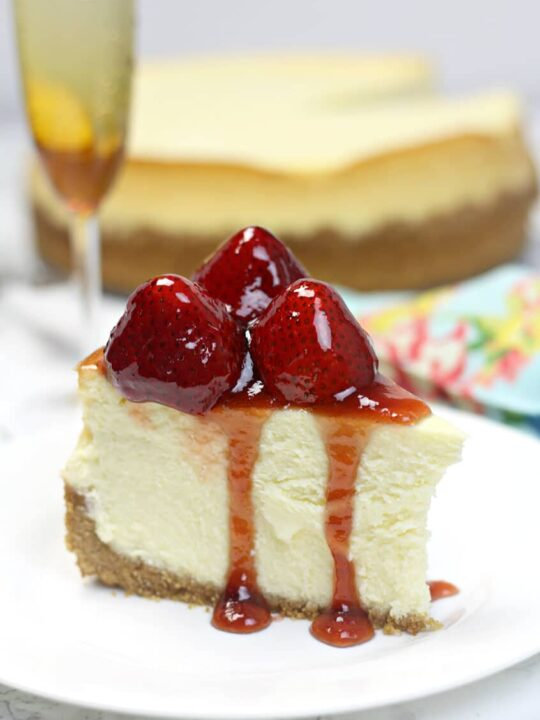 Side view of a slice of new york-style cheesecake with strawberries on top.