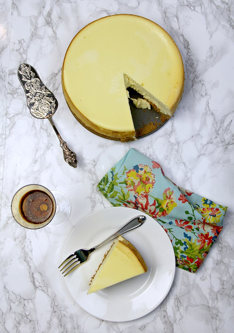 Overhead shot of a whole cheesecake and a slice on a plate.