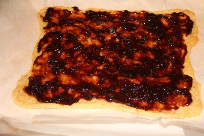 spreading fig jam on pizza crust