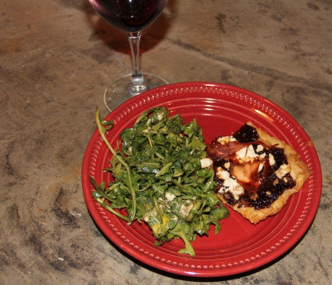 plate with slice of fig jam pizza and arugula salad