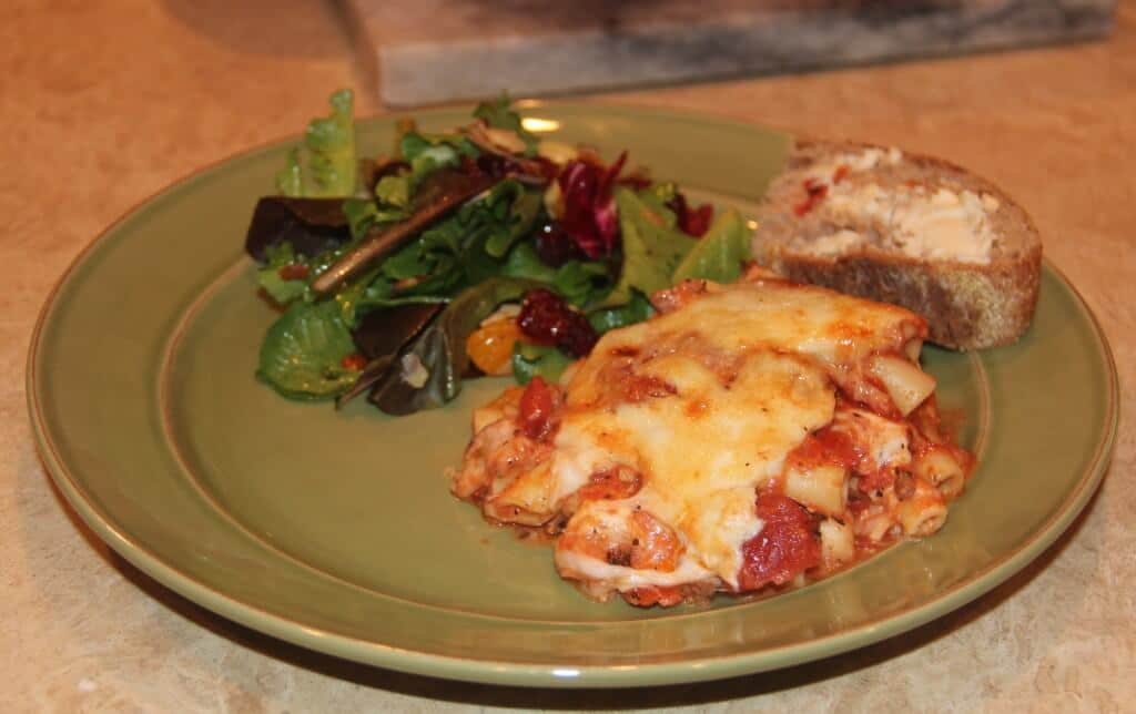 a green plate with baked ziti and salad
