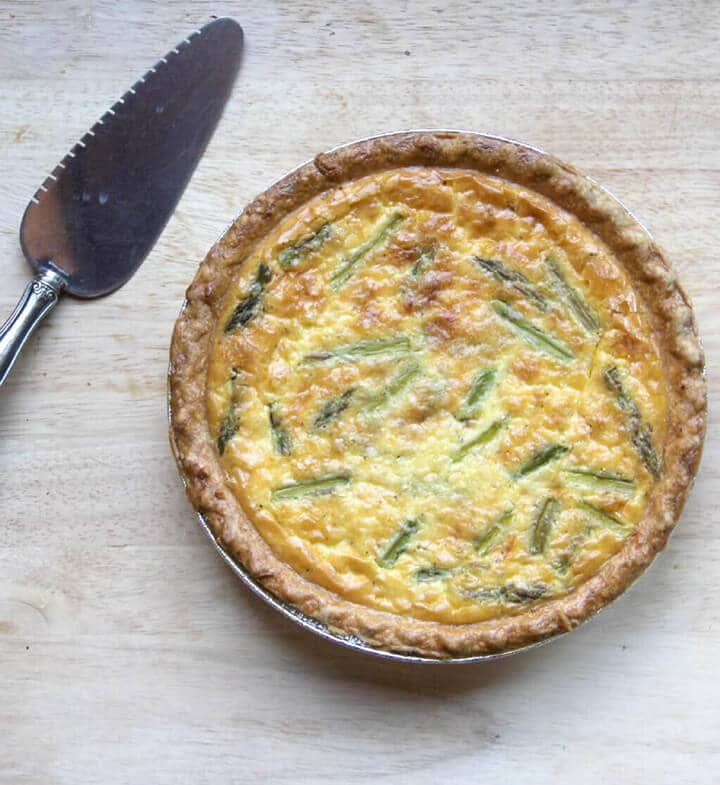 Overhead view of a whole quiche on a board with a serving spatula.