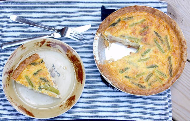 Whole quiche with a slice on a plate over a blue-striped towel.