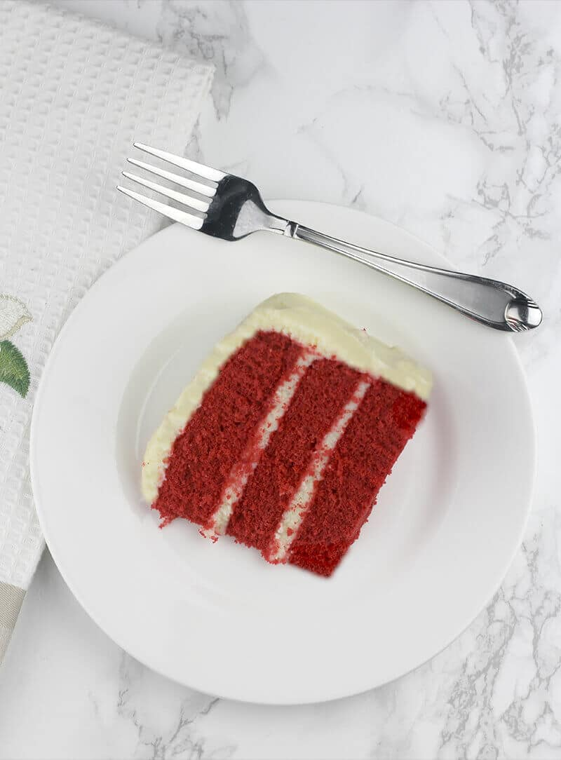 A slice of red velvet cake on a plate with a fork.