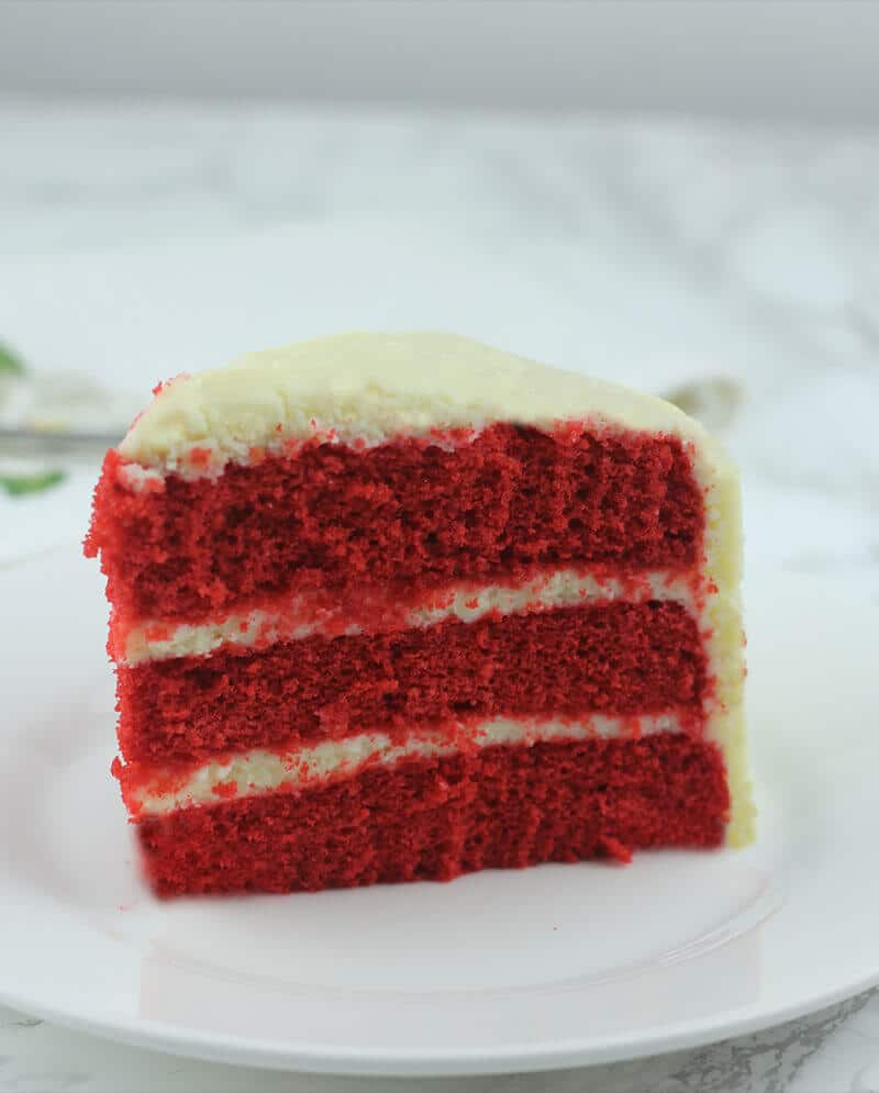 A slice of red velvet cake with cream cheese frosting on a plate.