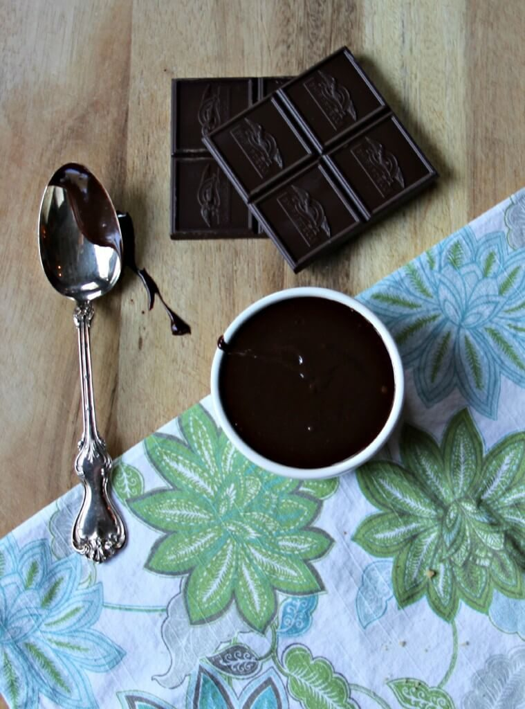 Bowl of chocolate ganache with a spoon and chocolate beside it.