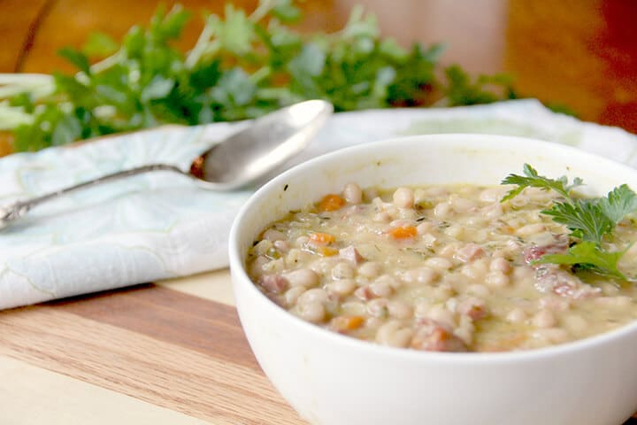Bowl of navy bean soup with parsley in the background.