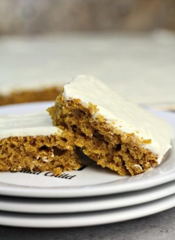 Two pieces of pumpkin sheet cake on a plate.