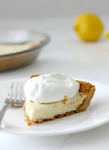 A slice of lemon icebox pie on a plate with a fork.