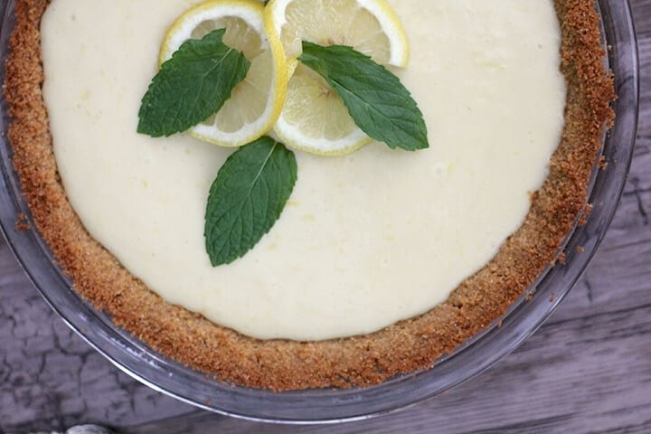 Lemon icebox pie eagle brand in a graham cracker crust with mint leaves as garnish on top.